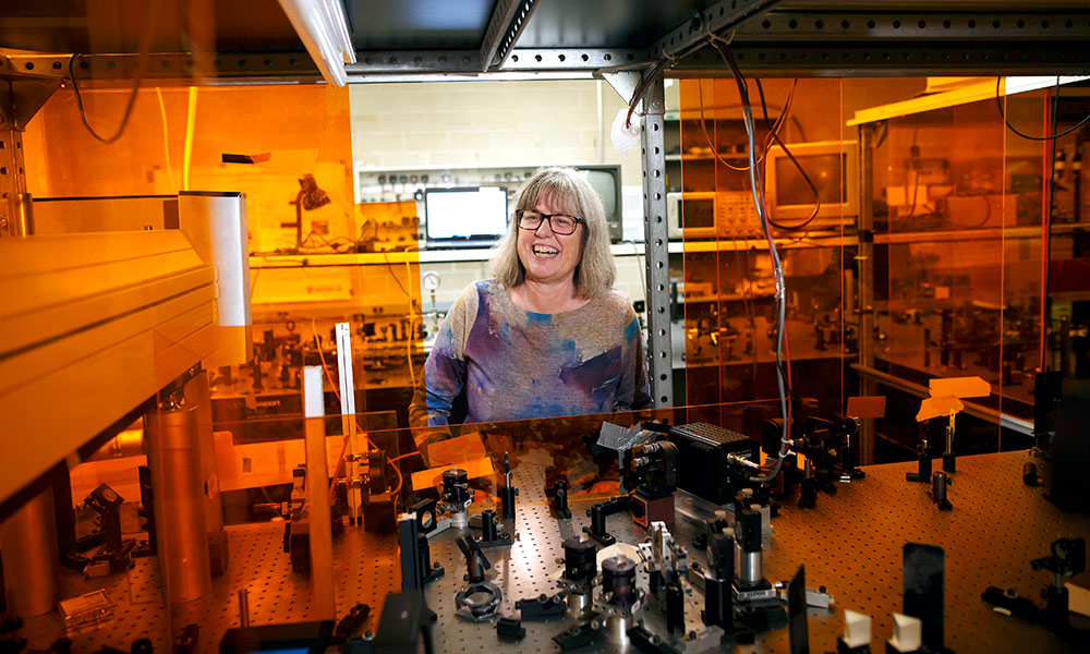 Donna Strickland in her lab surrounded by laser components and other optical devices