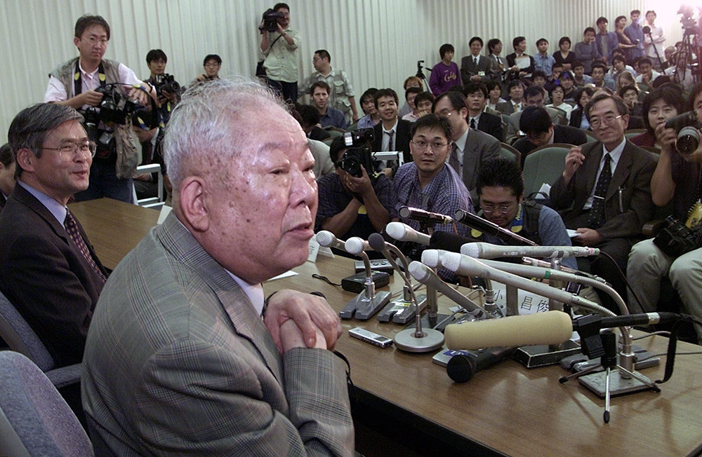 man at a table in front of mics and reporters