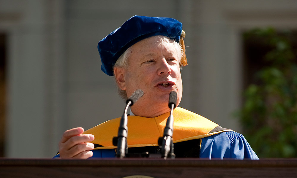man in academic robes speaking at a podium