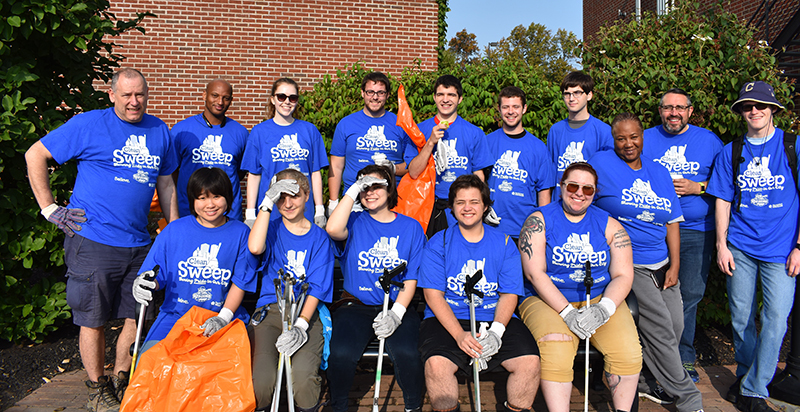 group photo of people in matching t-shirts and shovels and bags)