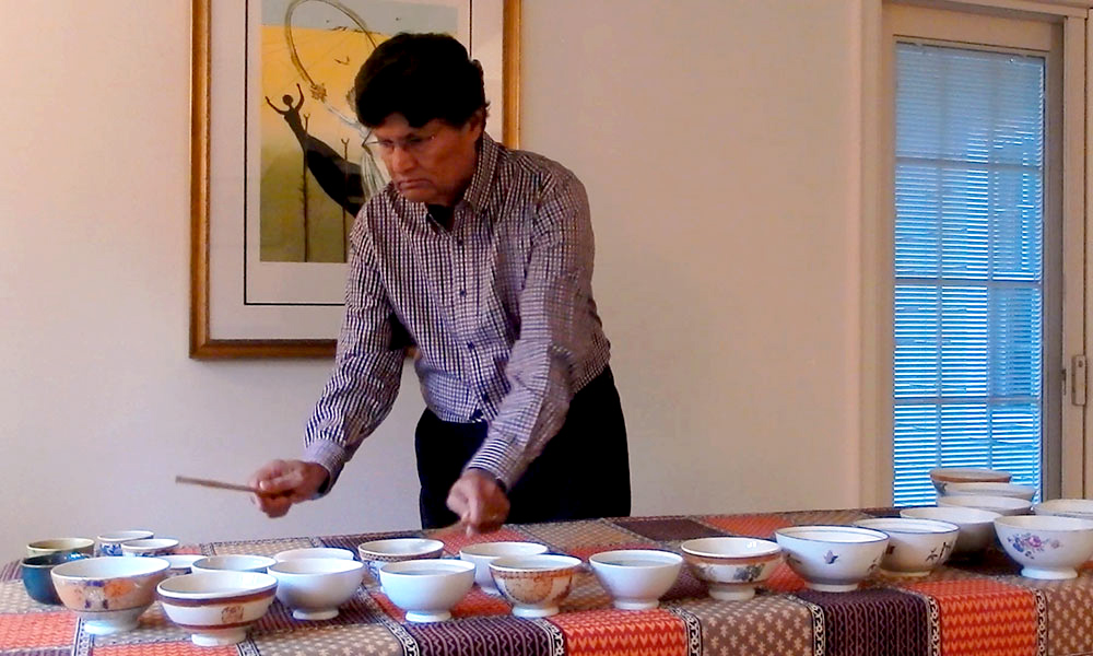 man playing an instrument made of bowls of water