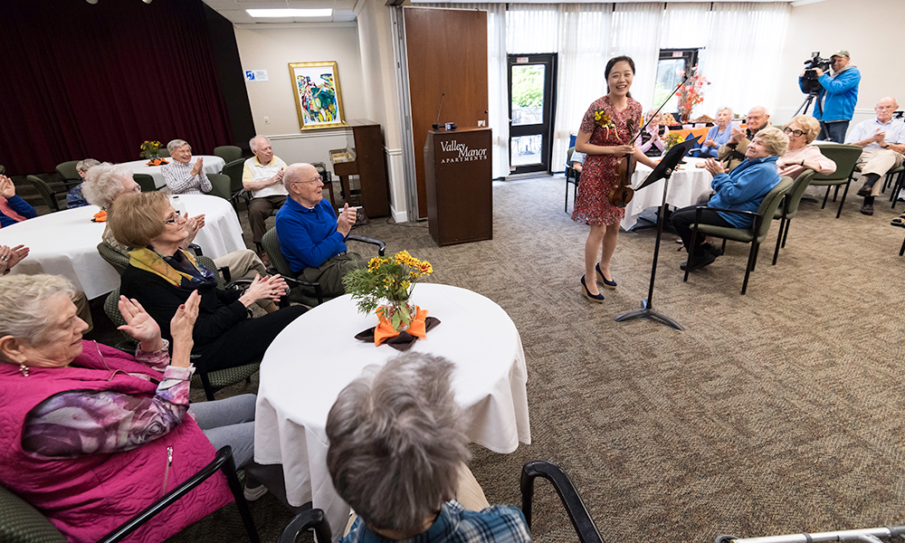 violinist bows before a crowd of senior citizens clapping