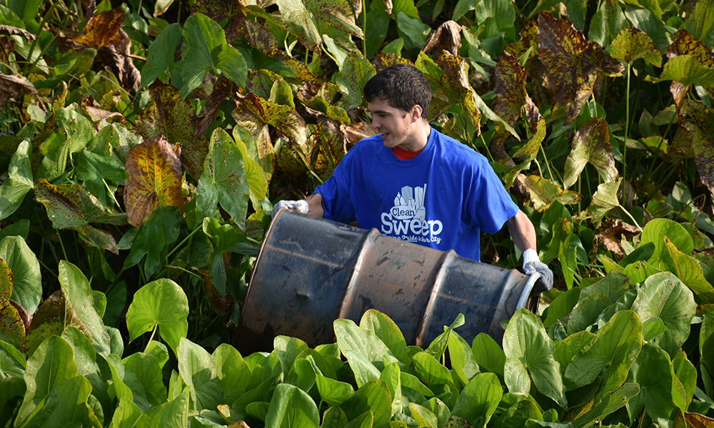 student lifting a barrel