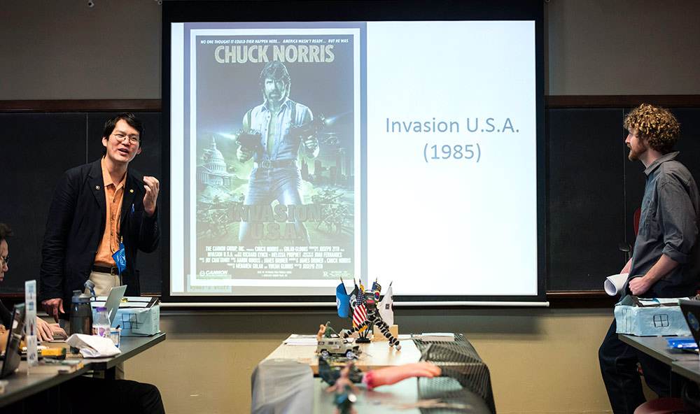 two instructors stand in front of a class with a screen showing a poster for the Chuck NOrris movie INVASION USA