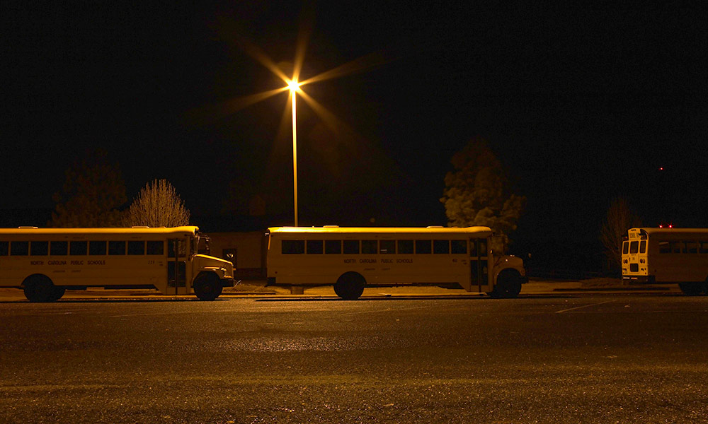 row of school buses at night