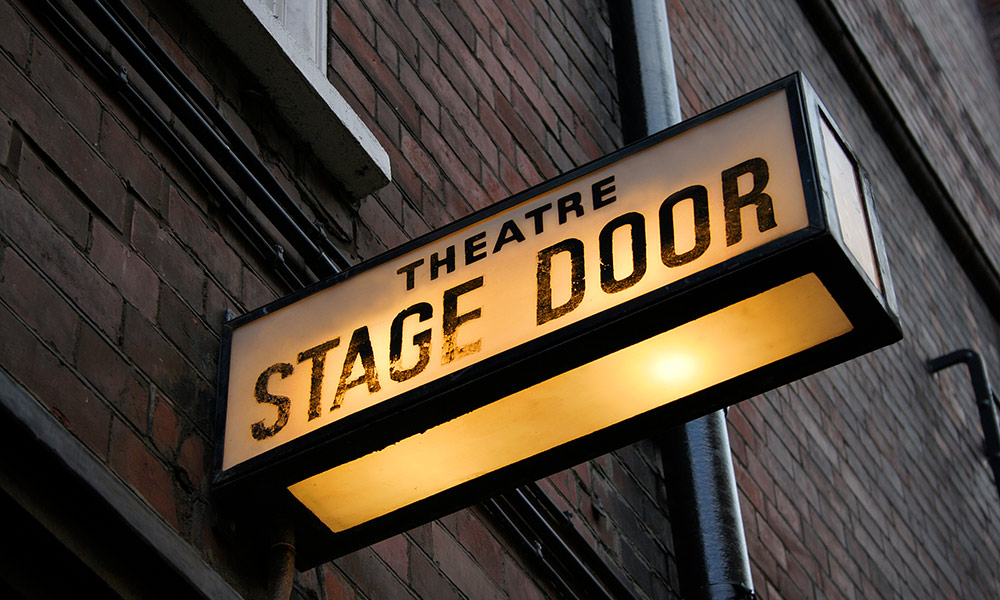 lighted sign reads STAGE DOOR