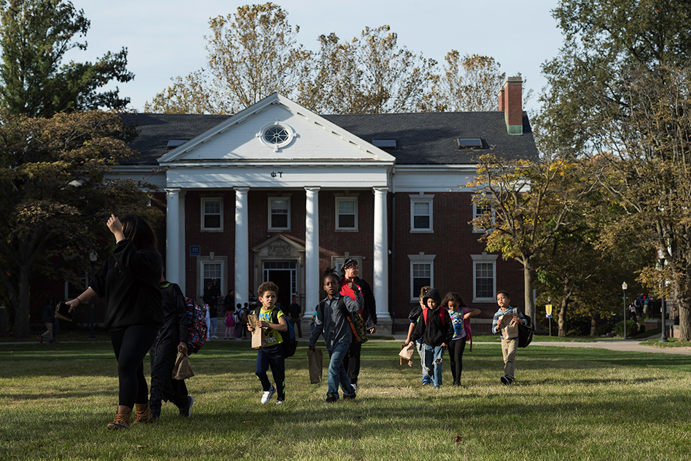 kids with trick or treat bags run across quad