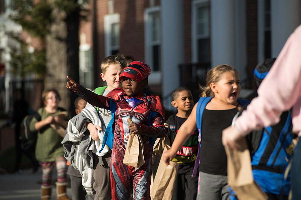 kids in Halloween costumes walk in a line across the quad