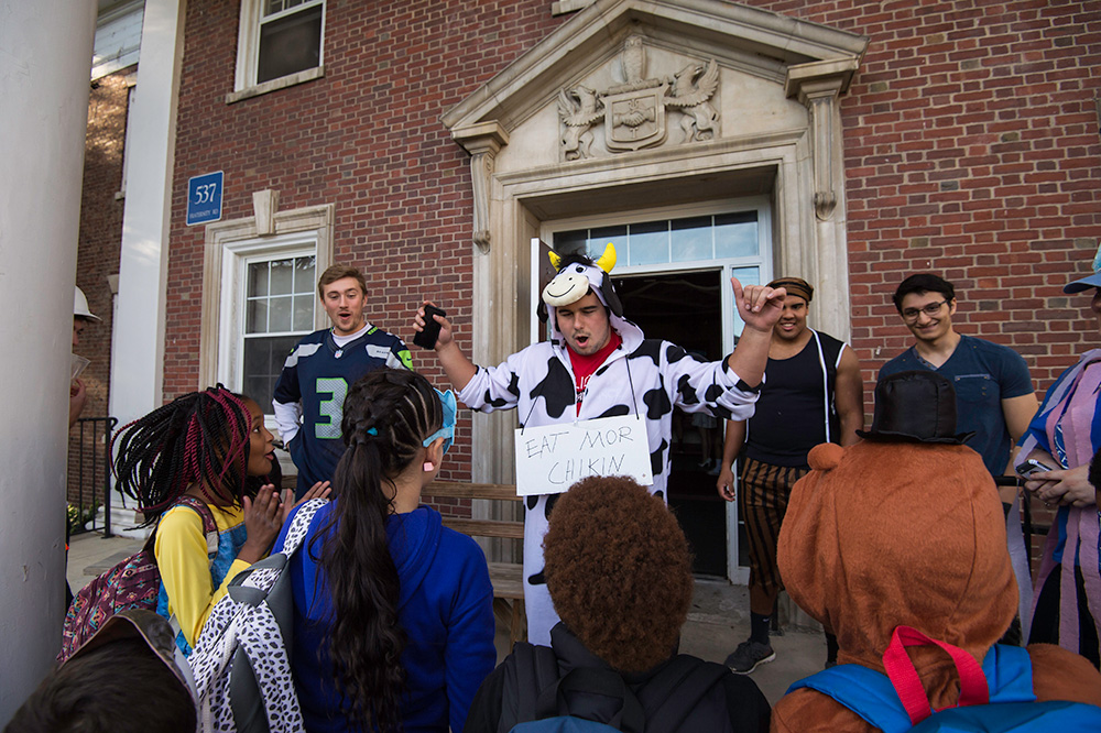 student dressed in cow costume speaks and laughs with a group of other students in front of a fraternity house