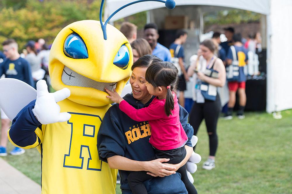 woman and child talking to a Yellowjacket mascot