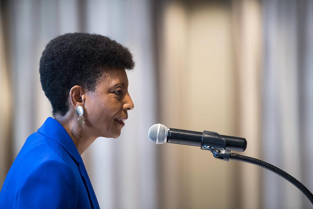 woman speaking behind a microphone