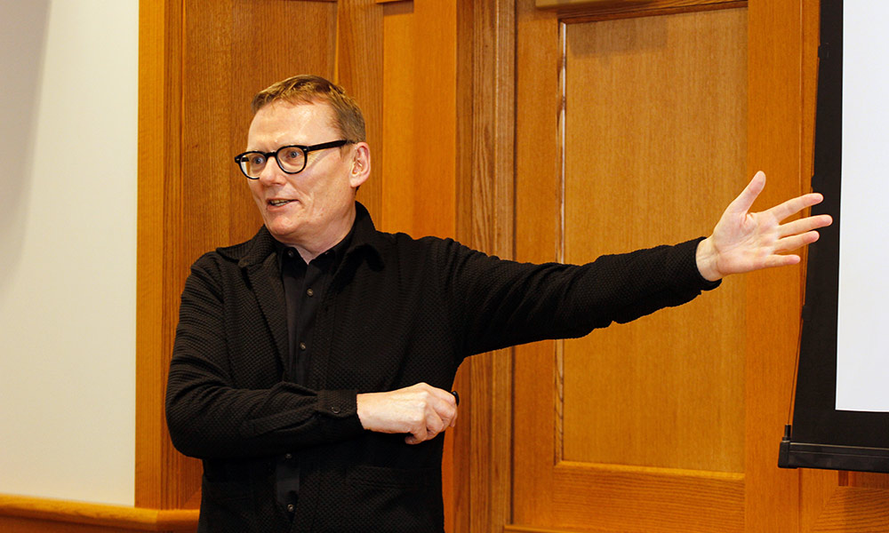 man gestures while speaking in front of audience in library