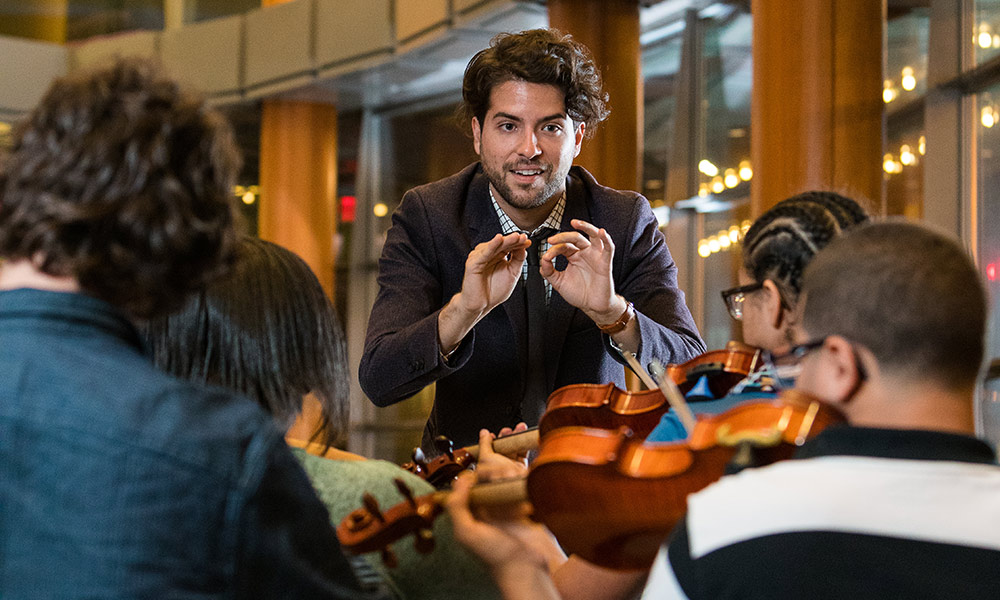 Alex Pena conducting an orchestra of kids