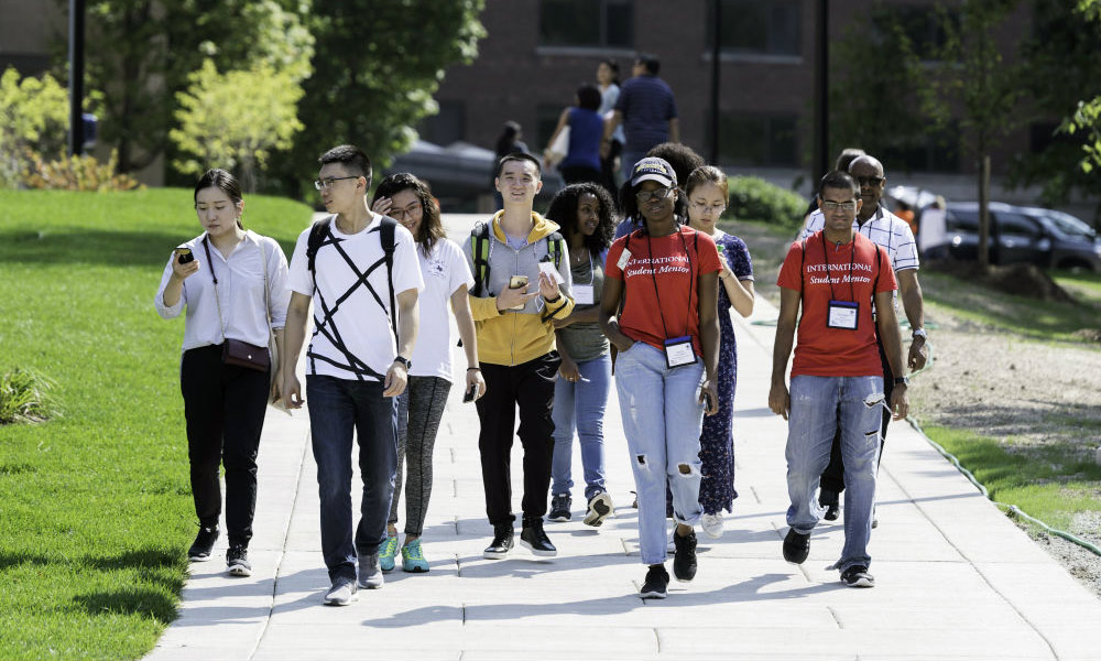 large group of students walking across campus