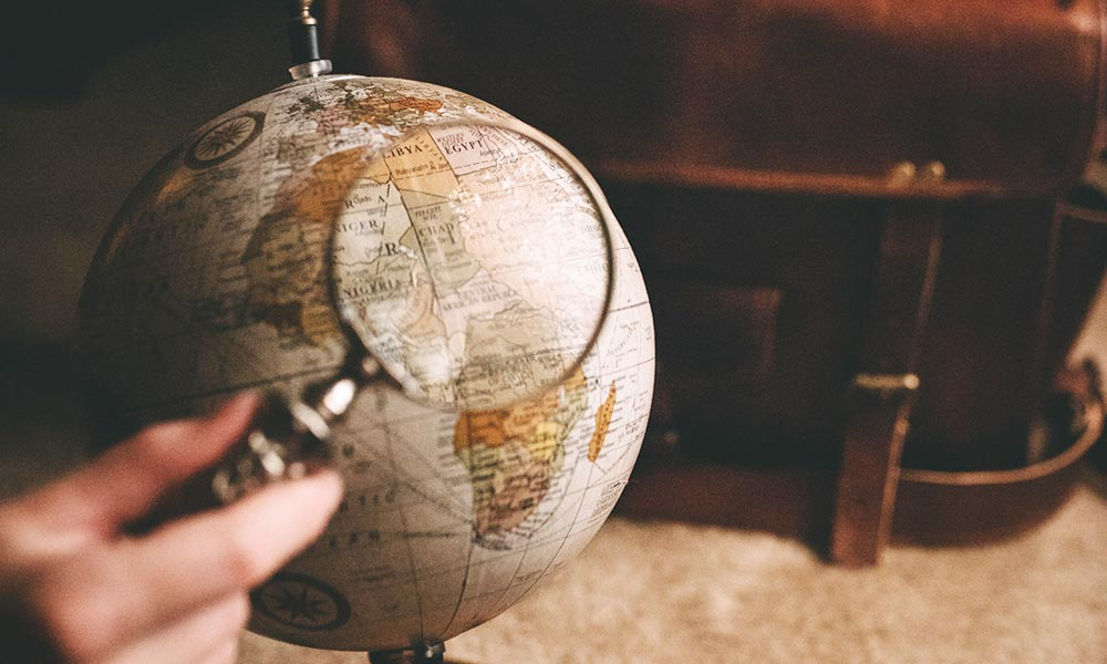 person holding a magnifying glass up to a globe