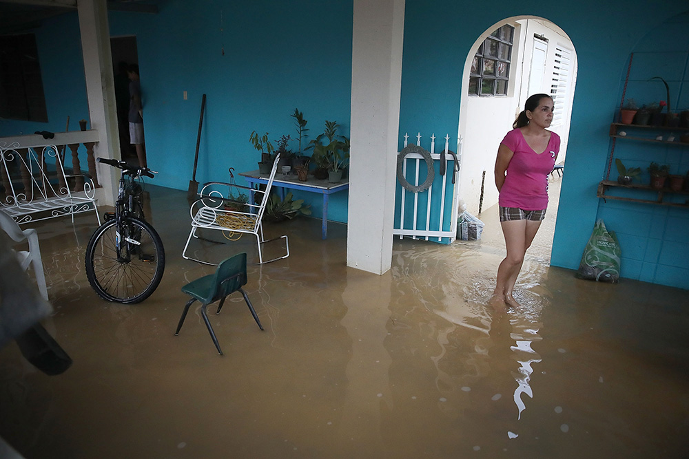 woman standing in water in her flooded home in Puerto Rico