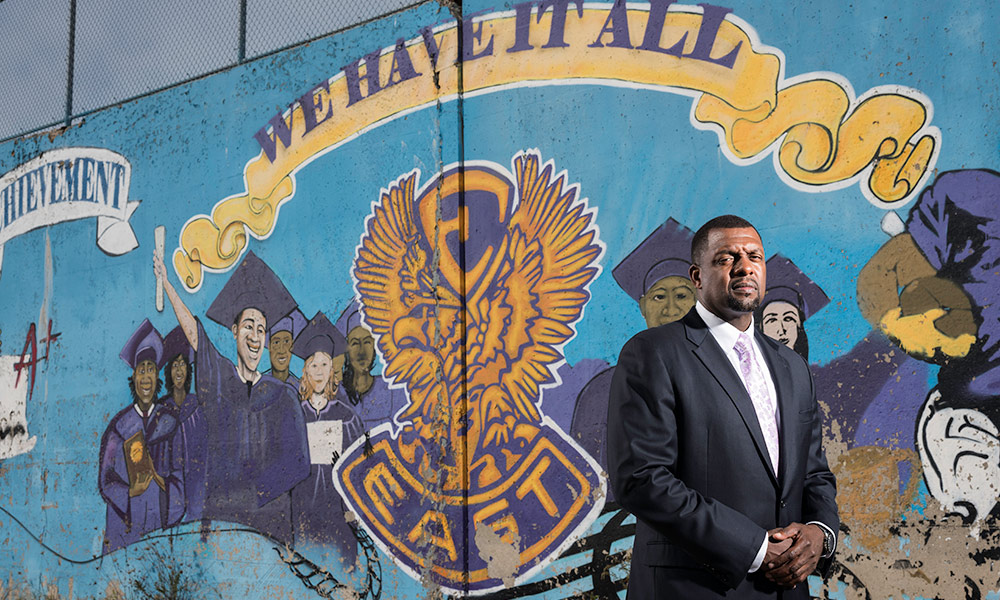 Shaun Nelms stands in front of a painted mural that reads WE HAVE IT ALL : EAST HIGH