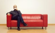 man sitting along on a red couch, drinking tea