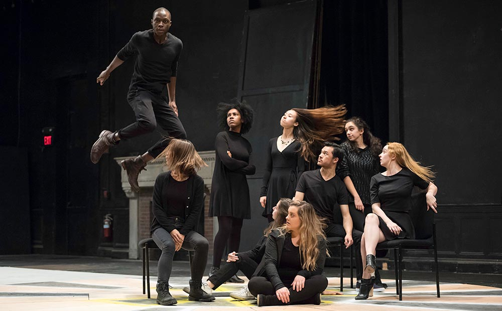 cast of actors on stage, one of them leaping through the air.