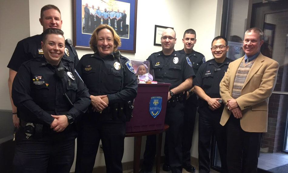 public safety officers smile and stand with a donation box