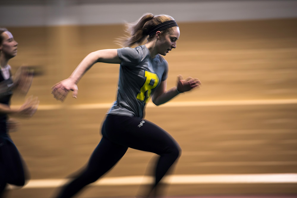 student athlete running on an indoor track