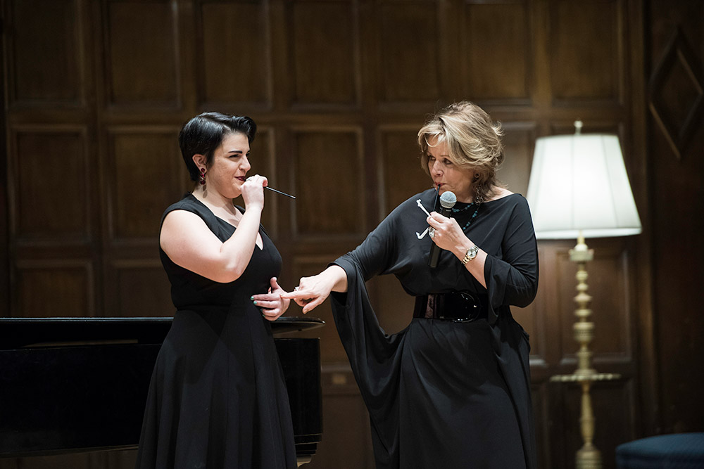 two opera singers on stage, one instructing the other, pointing to her diaphragm