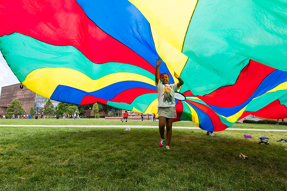 child playing under a colorful parachute