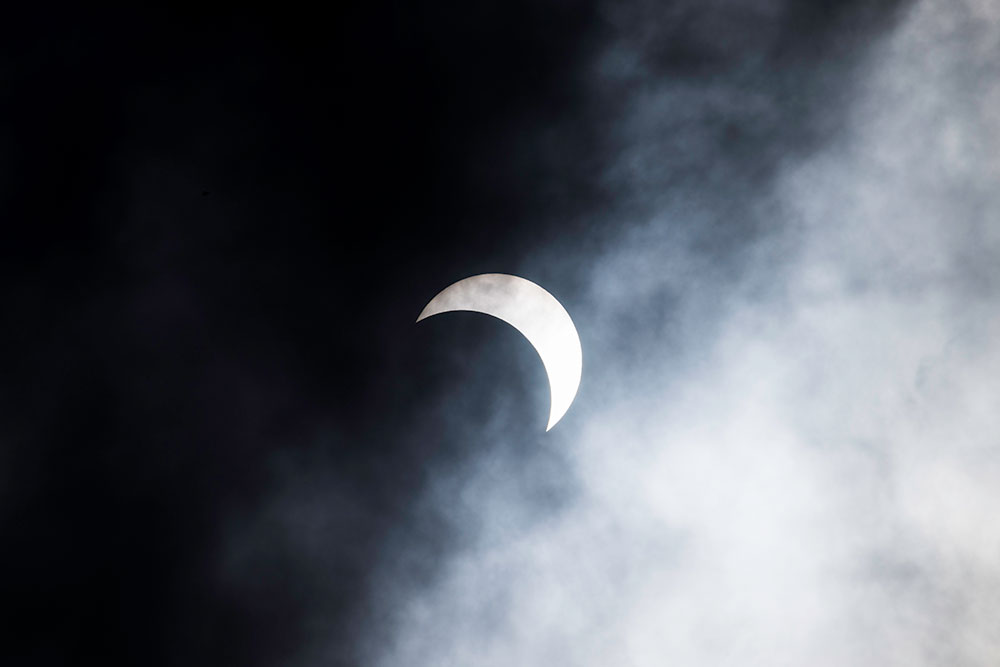 partial solar eclipse behind clouds