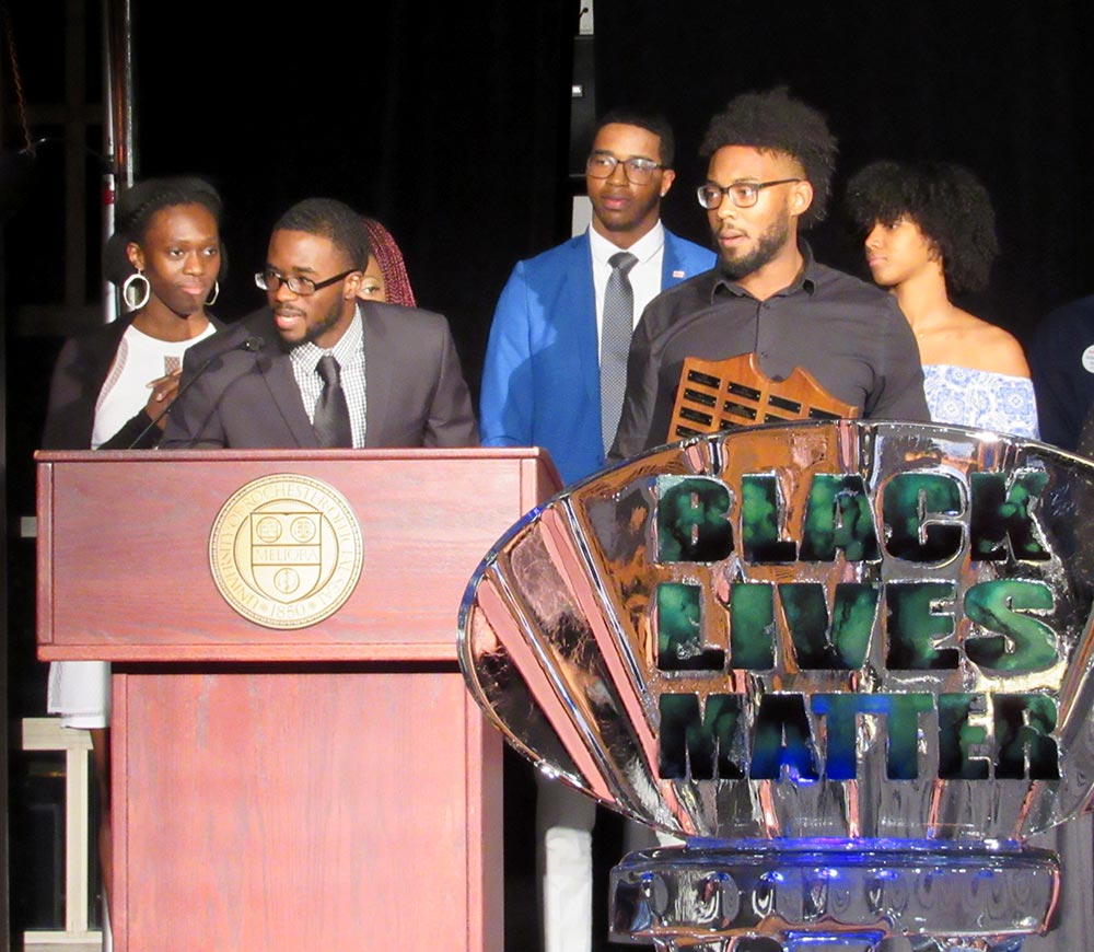 Group of students speak behind a podium behind an ice sculpture that reads BLACK LIVES MATTER