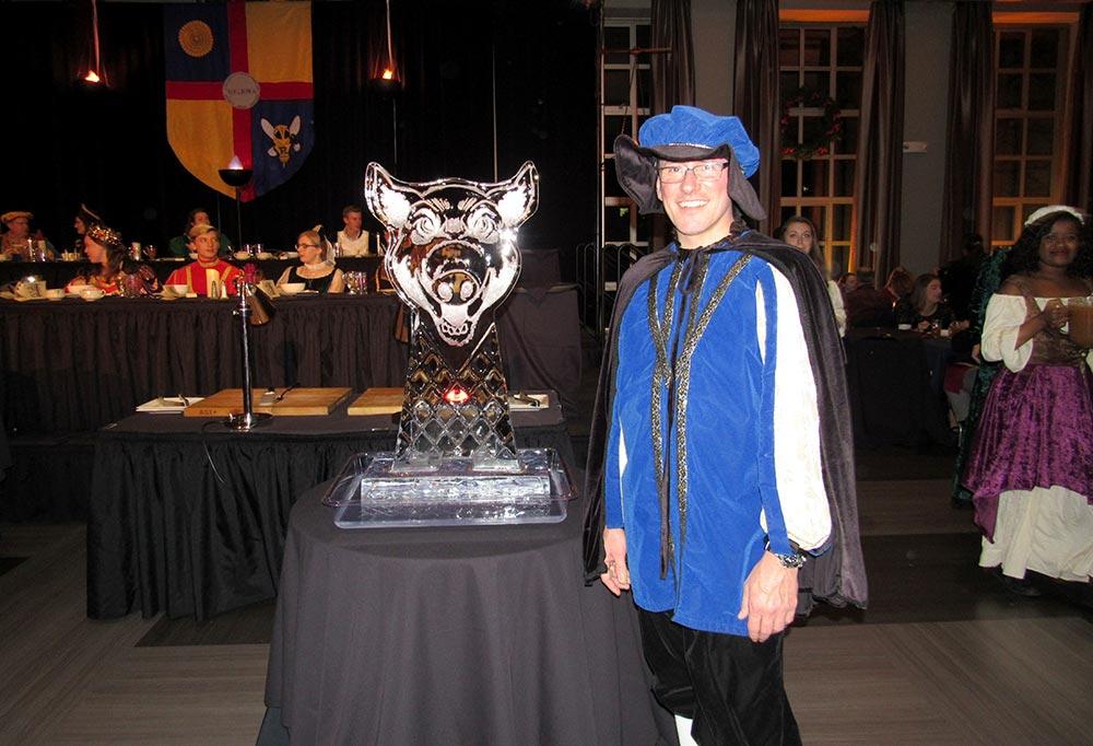 Dean Matt Burns next to ice sculpture of boar