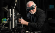 Wayne Knox wearing goggles in his optics lab
