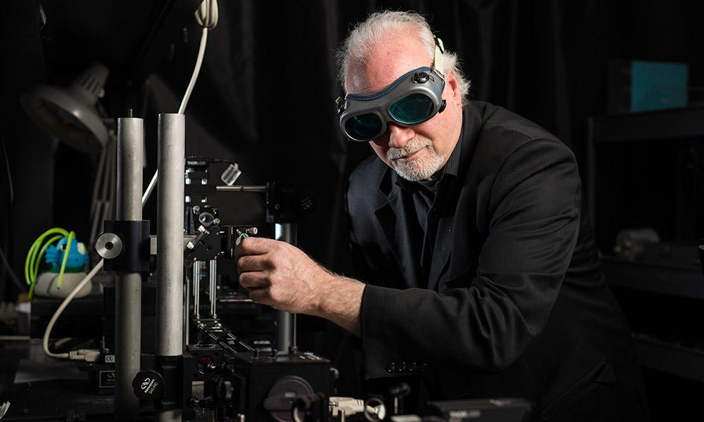 Wayne Knox wearing goggles in his optics lab