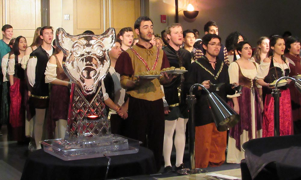 singers in costume carrying food at Boar's Head Dinner