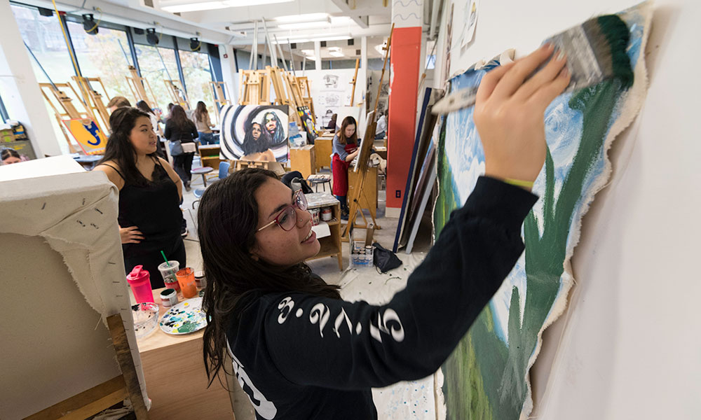 students painting in a busy art studio