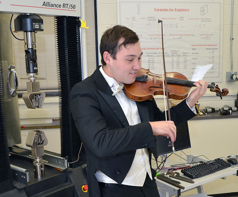 student playing the violin in an engineering lab