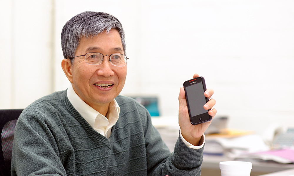 smiling professor holding a cellphone