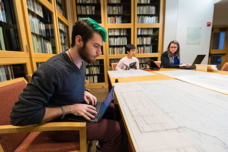 student with laptop looks at architectural drawings