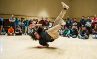 man breakdancing in front of a crowd