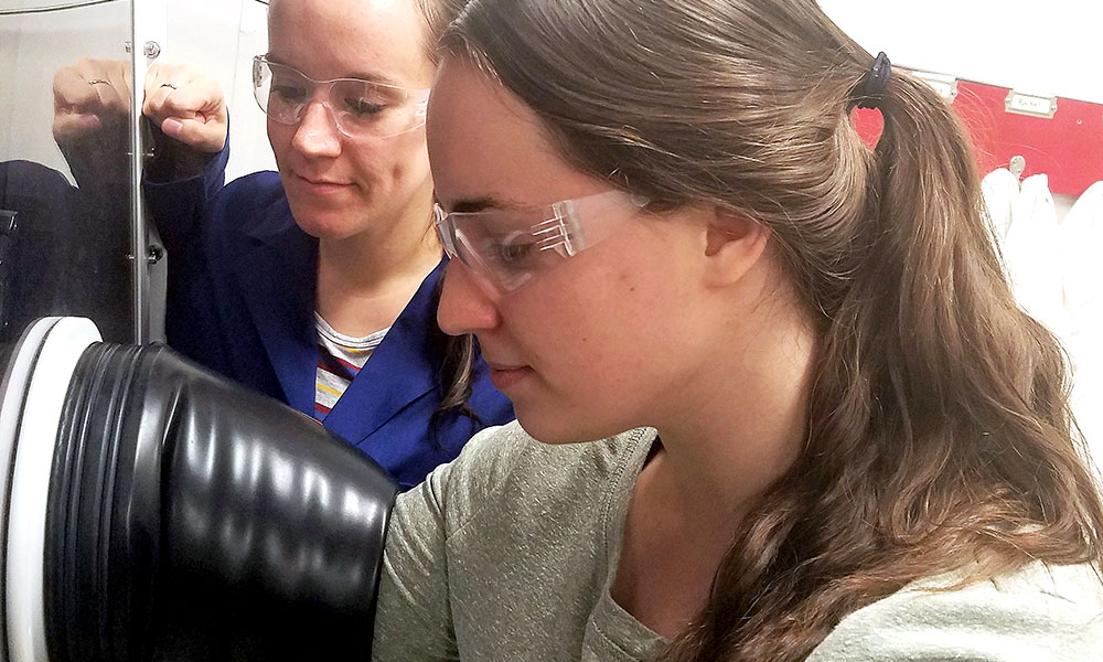 two researchers in a lab, manipulating materials behind a screen