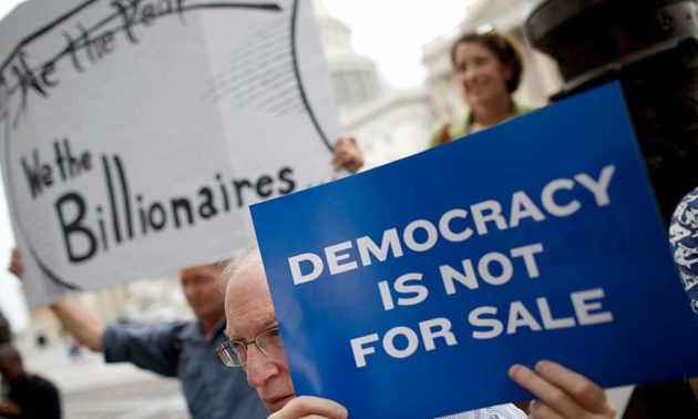protester holding a sign that reads DEMOCRACY IS NOT FOR SALE