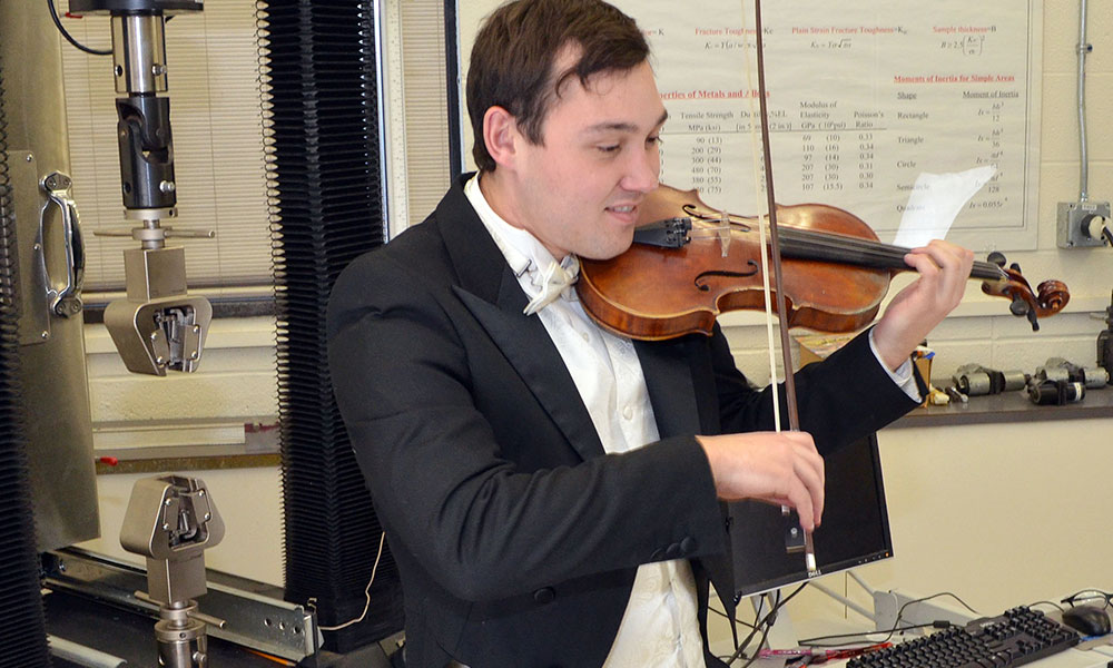 student in a tuxedo plays the violin in a mechanical engineering lab