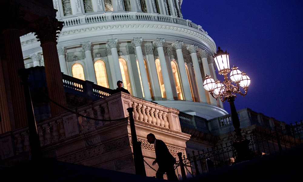 the Capitol building at night, with a single person running up the stair