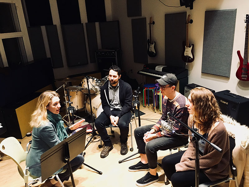 Four people sitting around microphones in a recording studio