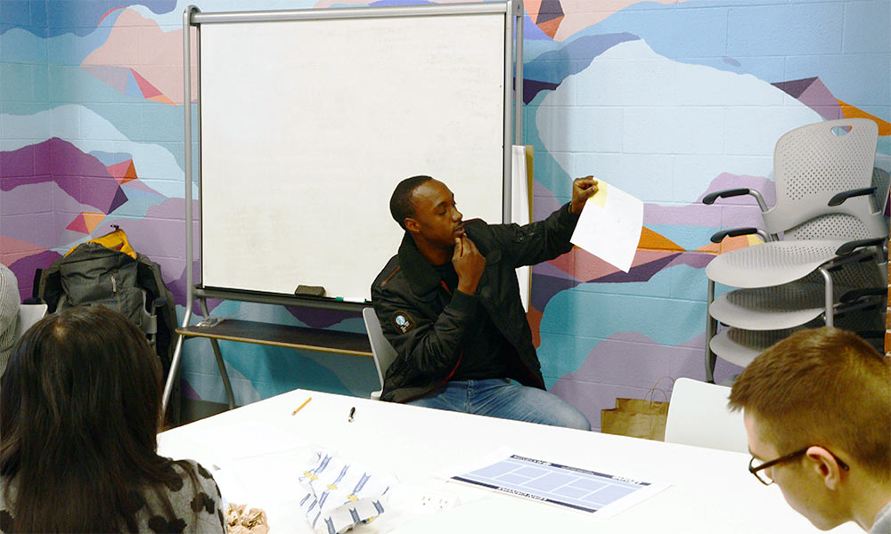 A student leading a discussion in a room with whiteboards and brightly painted walls in Rush Rhees Library