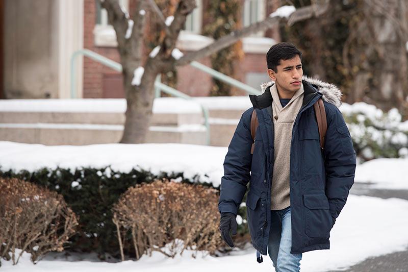 young man walking through a snowy quad