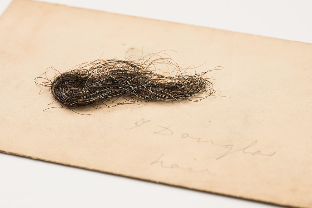 lock of hair on a piece of paper with the hand written words Frederick Douglass
