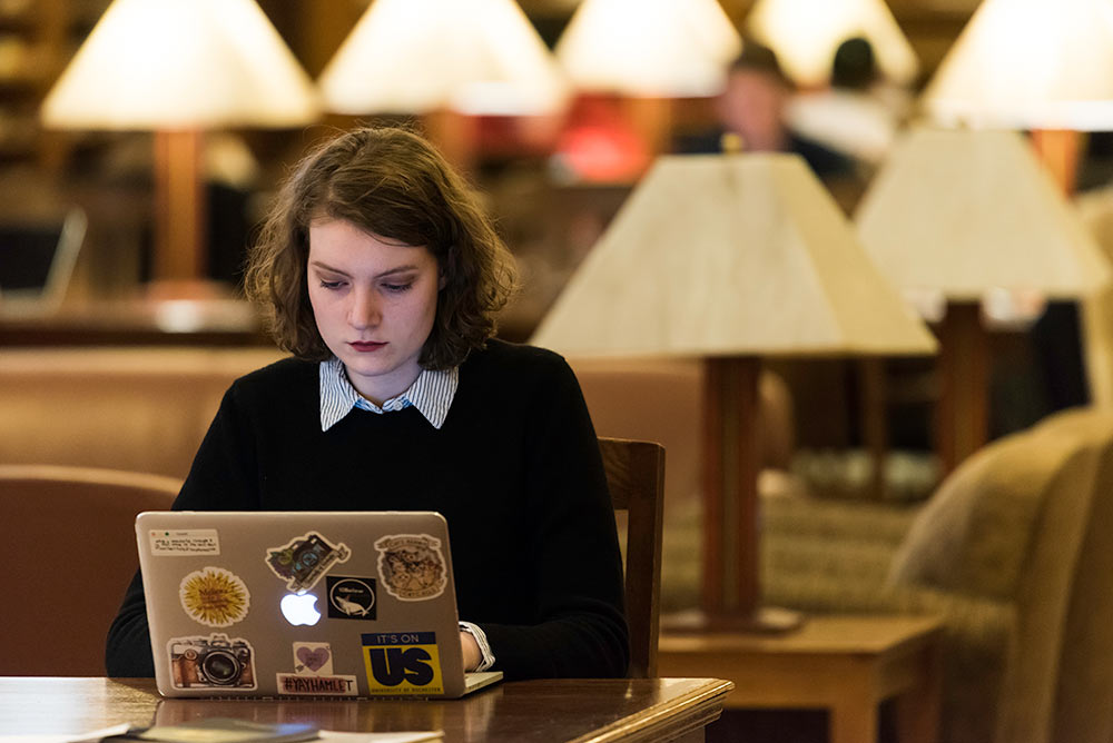 young woman with her sticker covered laptop in a library