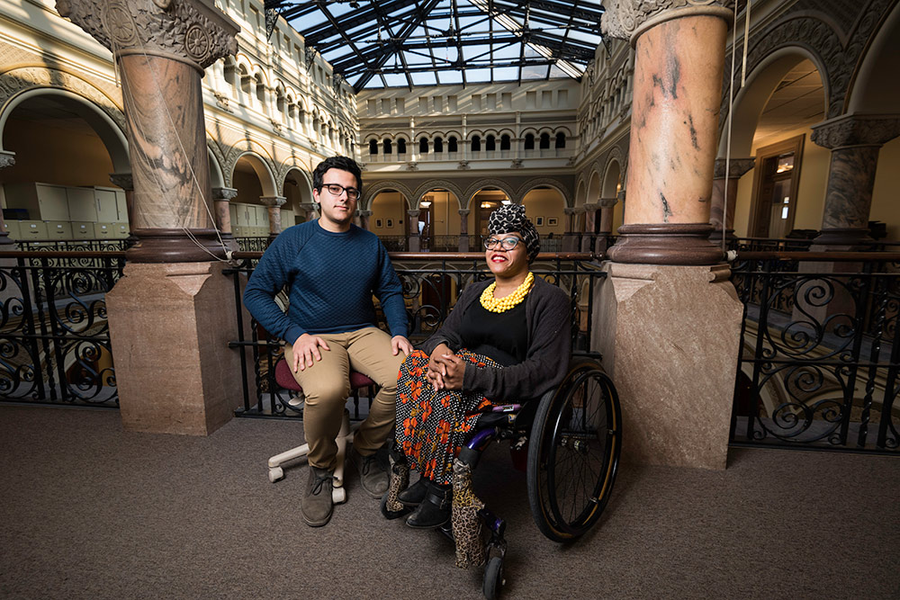 young man and woman in a wheelchair pose for a photo in City Hall