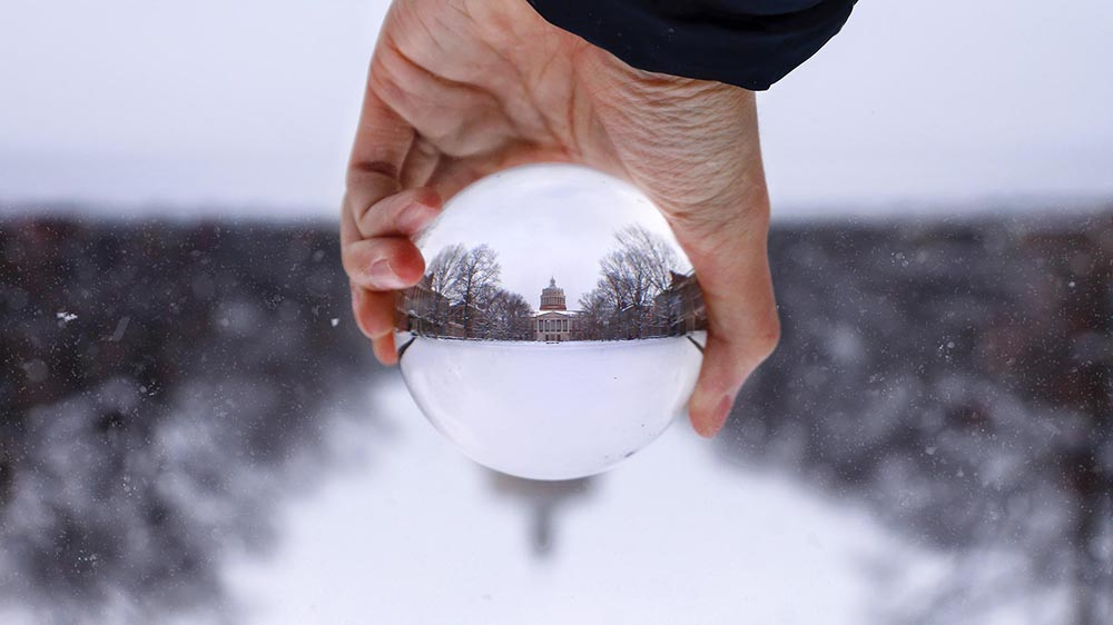 photo showing Rush Rhees Library in the snow, reflected upside down in a glass globe