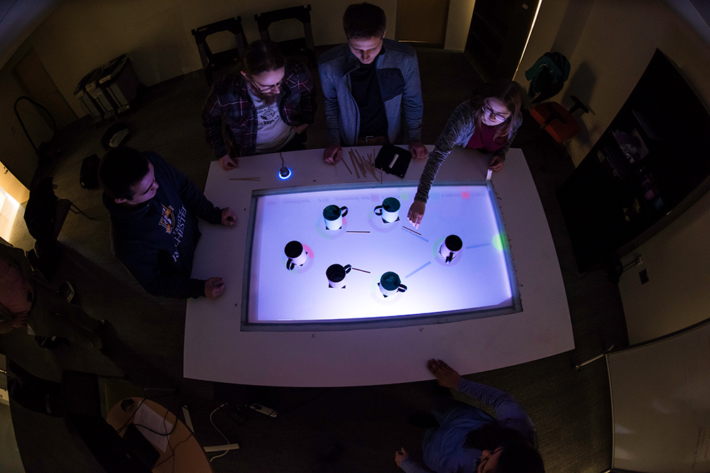 students moving coffee mugs around on a lighted table surface